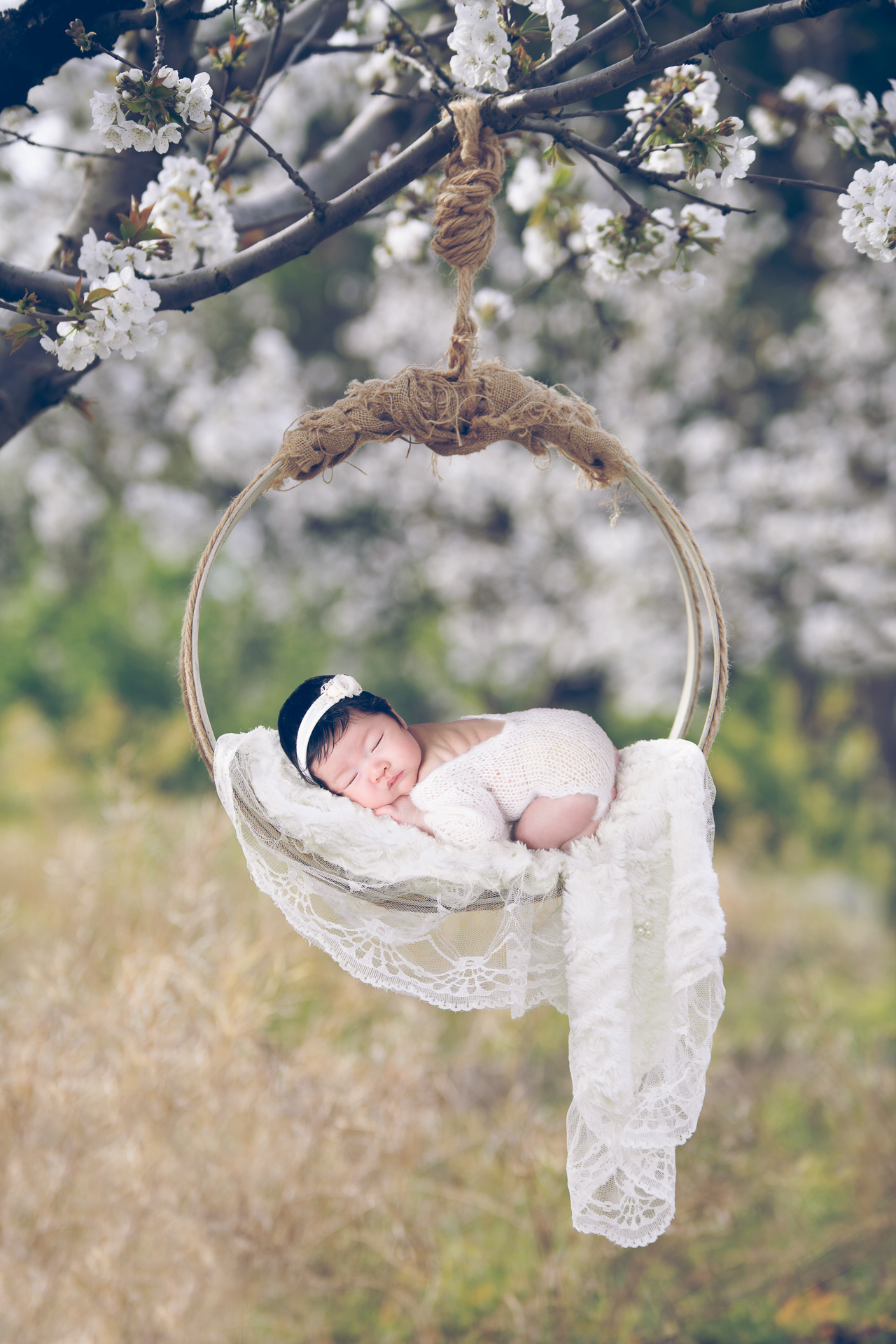 Newborn rests outdoors on hanging prop while wearing white outfit and white headband. White flowers decorates the scene.