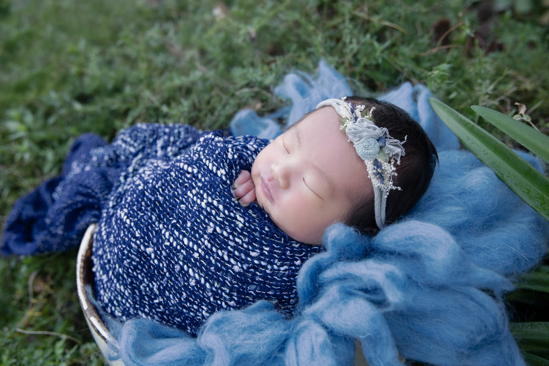 Newborn wearing blue headband and blue wrap rests on blue round basket decorated with blue carpet outdoors.