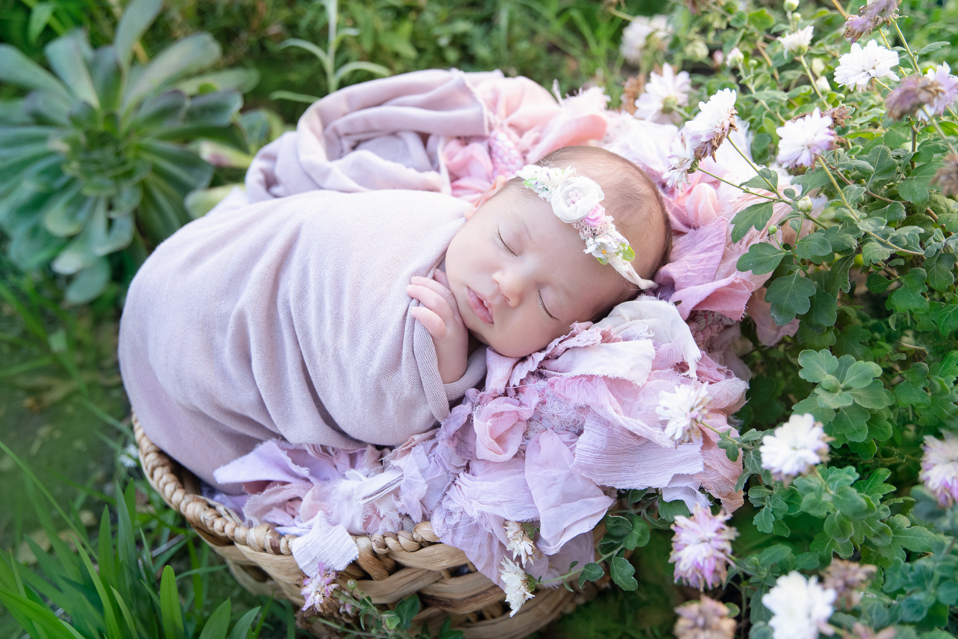 Newborn wearing pink headband and pink wrap rests on a round prop decorated with pink carpet outdoors.