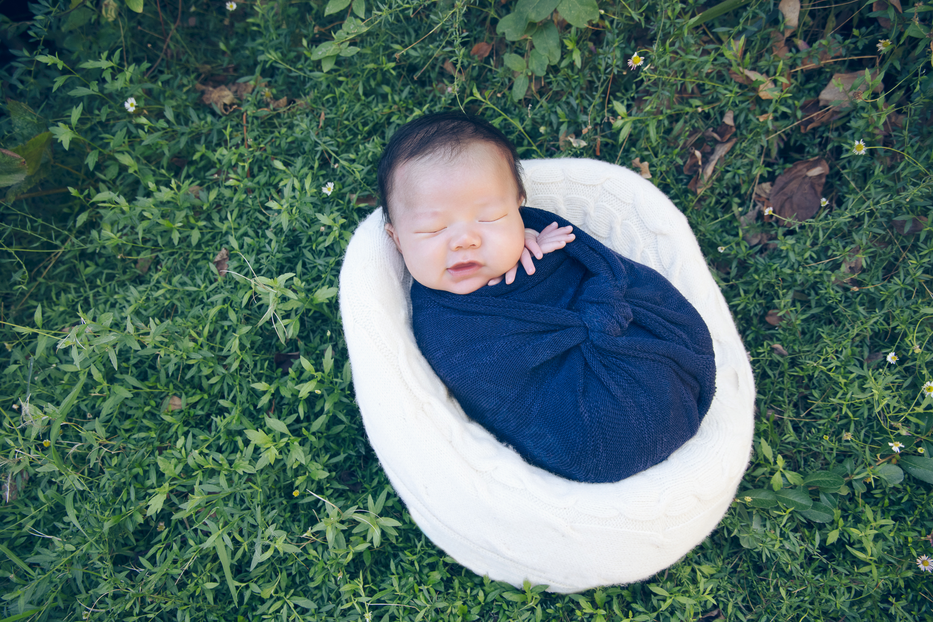 newborn wearing blue wrap rests on round shaped white prop outdoors.