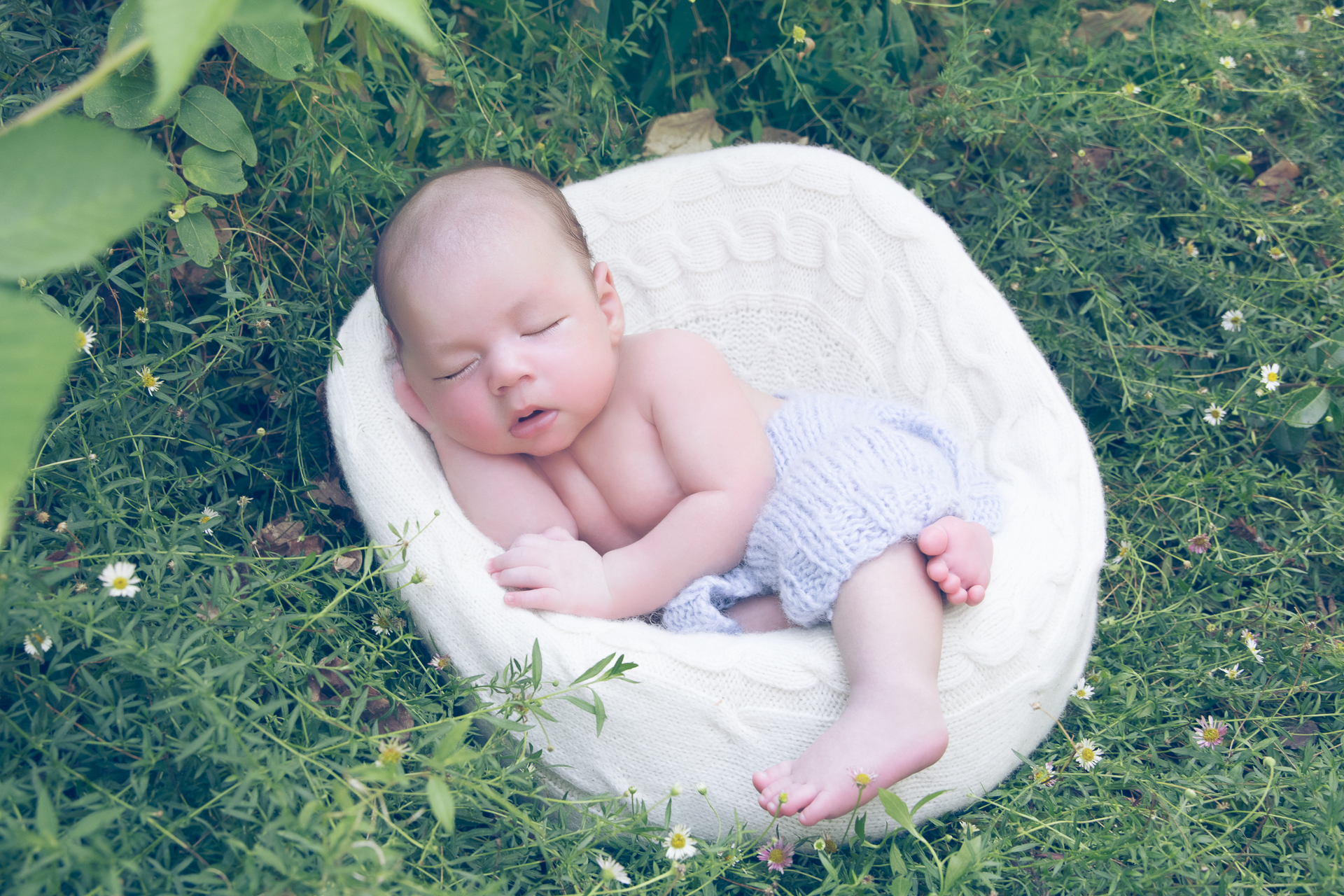 Newborn wearing light blue pants rests on white round prop outdoors.