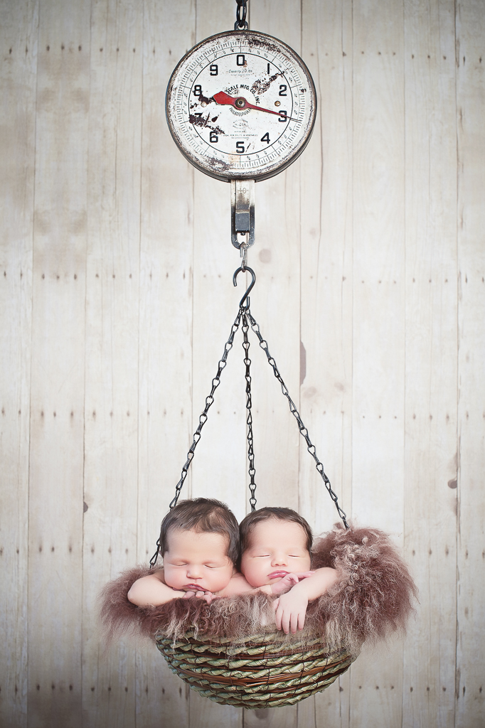 2 newborn siblings rest together on a basket hanging from a scale