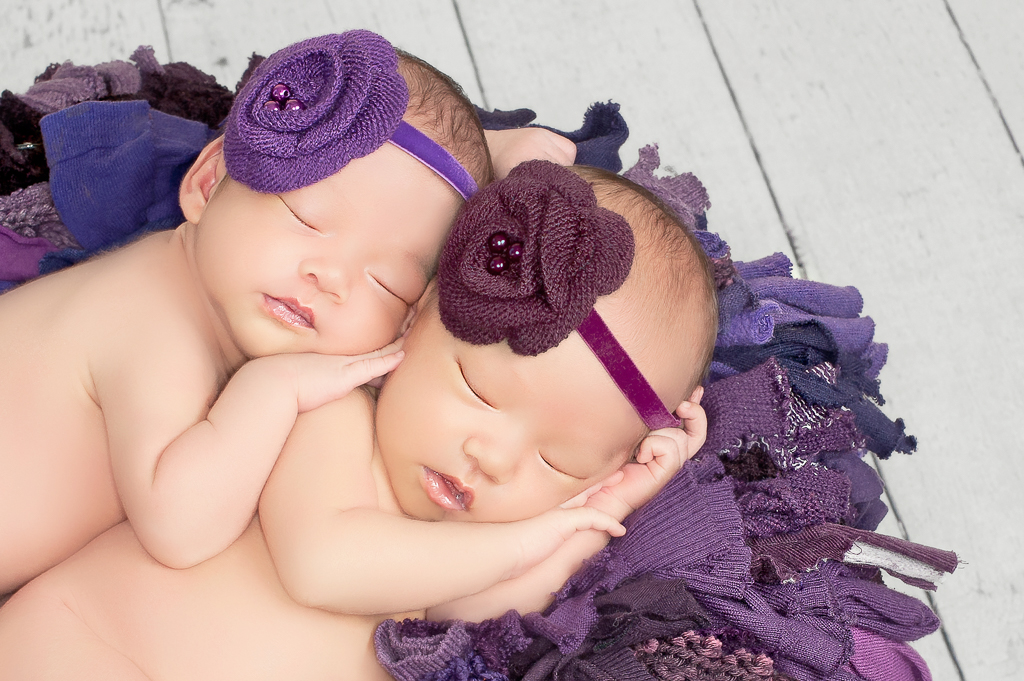 two newborn siblings rest together on a prop basket while wearing purple headbands, light color background