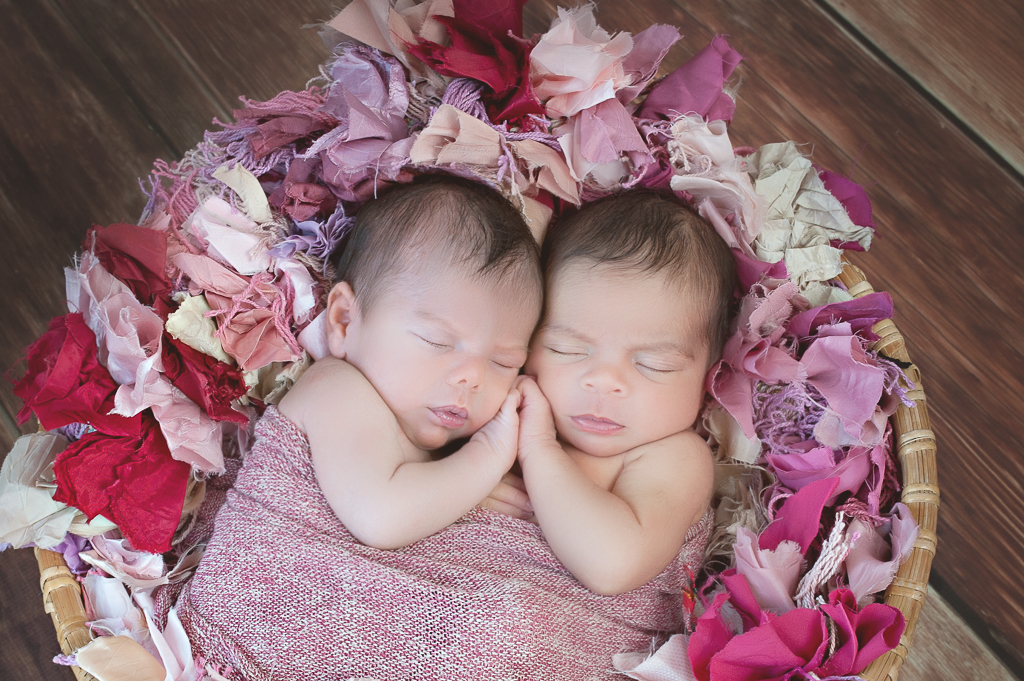 two newborn babies rest together on a prop basket. brown background, pink tones colorful carpet decorates the basket, babies shared light red and white wrap
