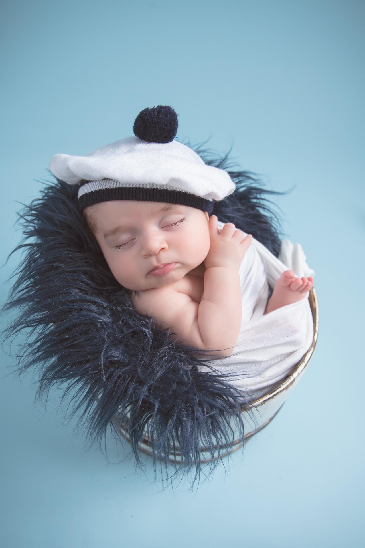 Older newborn rests on round basket prop. Blue backdrop. White and blue hat. White wrap.