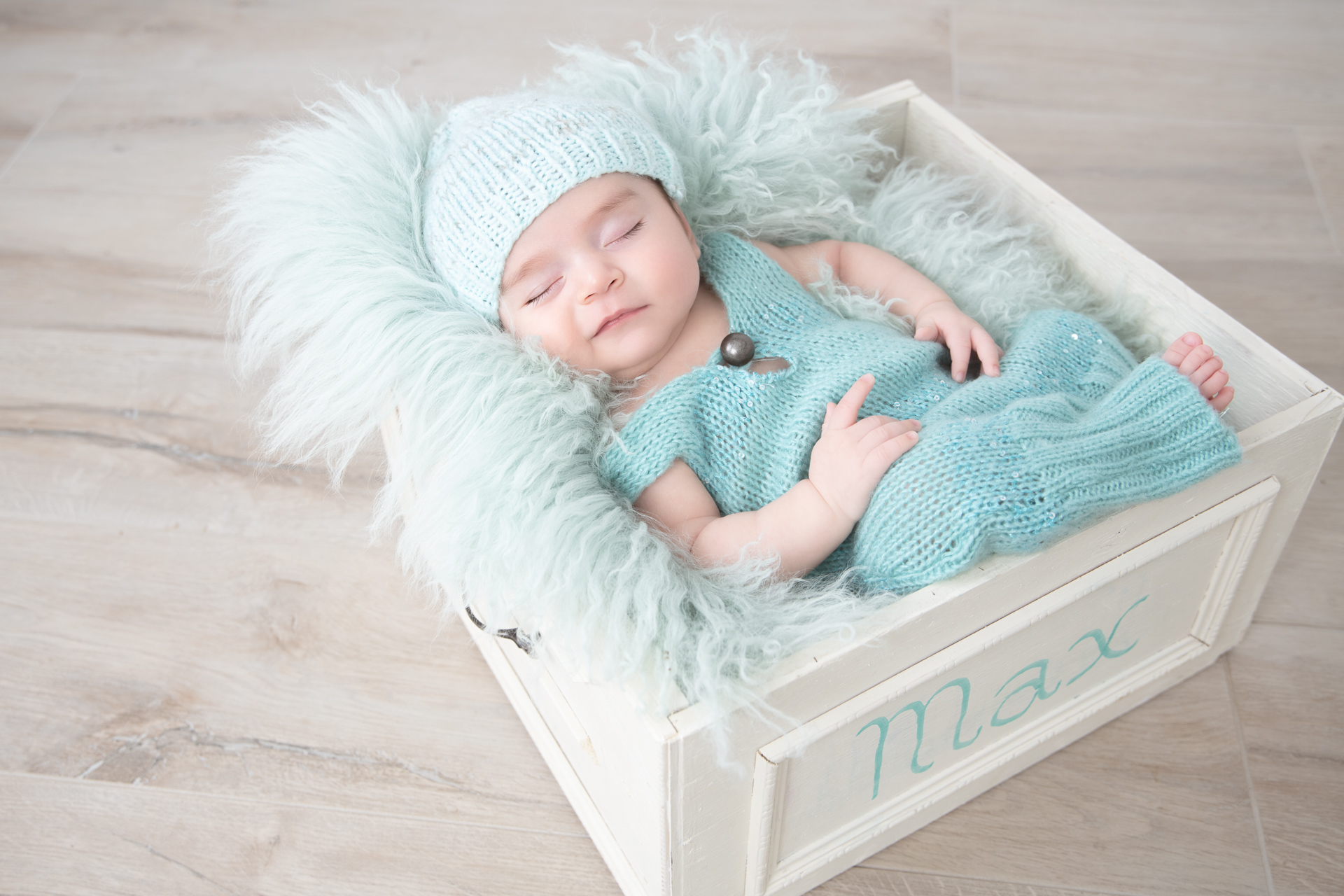 """Older newborn in green outfit and light green hat rests on square white basket prop. Basket shows the name """"Max"""". Light green fluffy carpet decorates the basket."""