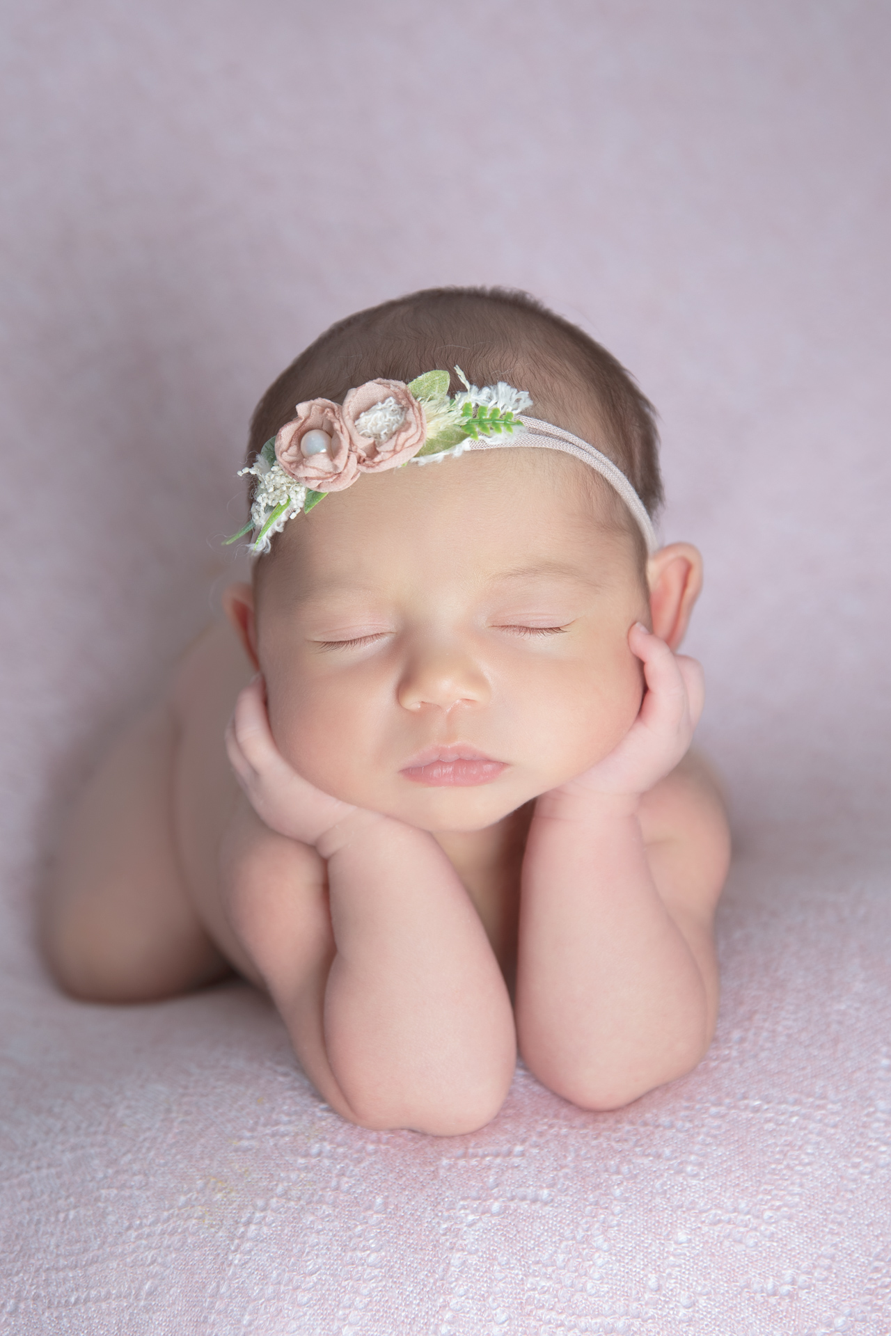Newborn wearing pink headband rests with both hands holding her head up on pink backdrop.