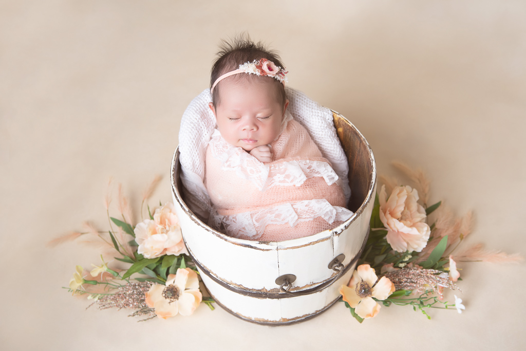 Newborn rests while wearing pink wrap and pink headband on a round prop. Beige backdrop. Flowers decorate the scene.