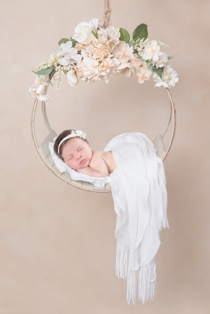 Newborn wearing white headband and white wrap rests on a round shaped hanging prop decorated by flowers. Beige backdrop.