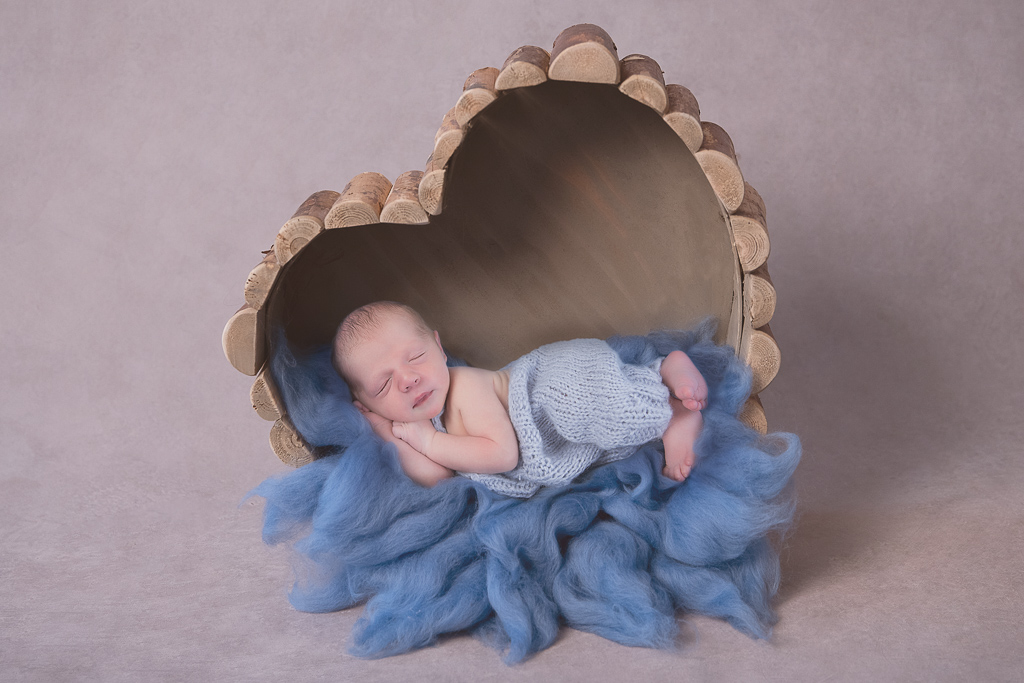 Newborn rest on wood heart shaped prop while wearing light blue outfit. Blue carpet decorated the scene. Light gray backdrop.