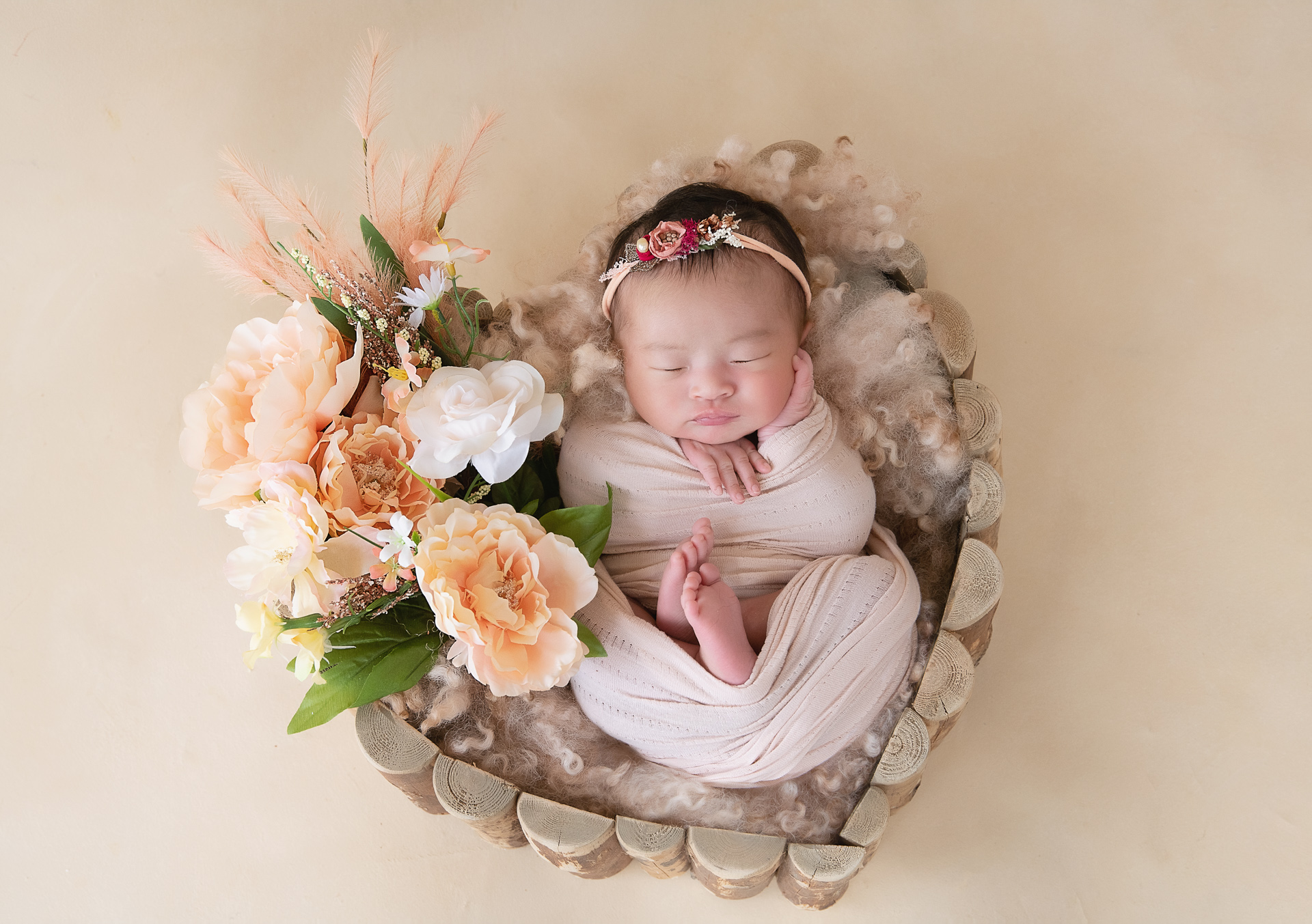 Newborn on light pink wrap and headband rests on heart shaped wood prop. Flowers decorate the scene. Beige backdrop.