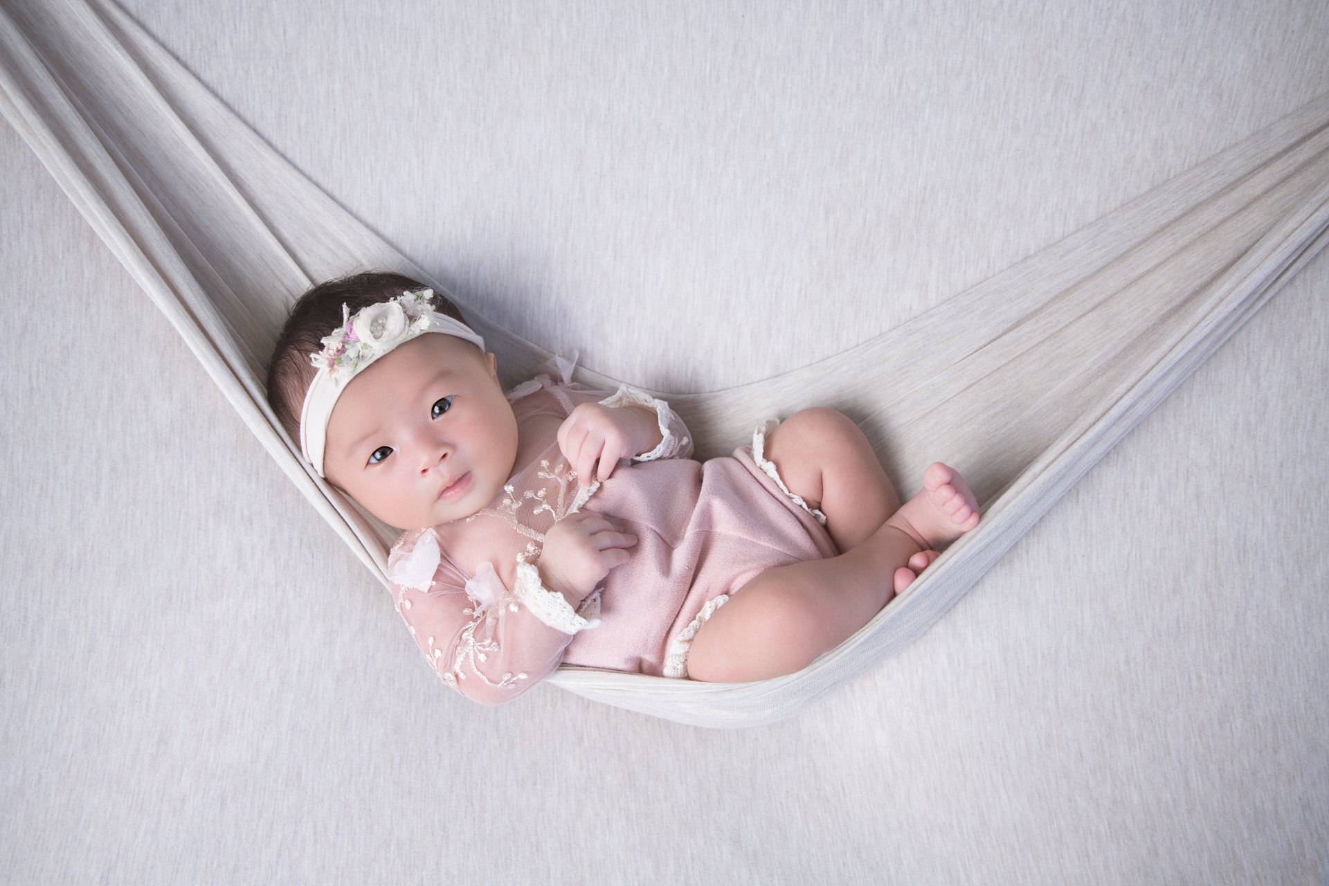 Newborn on light pink outfit looks at the camera. Light gray backdrop.