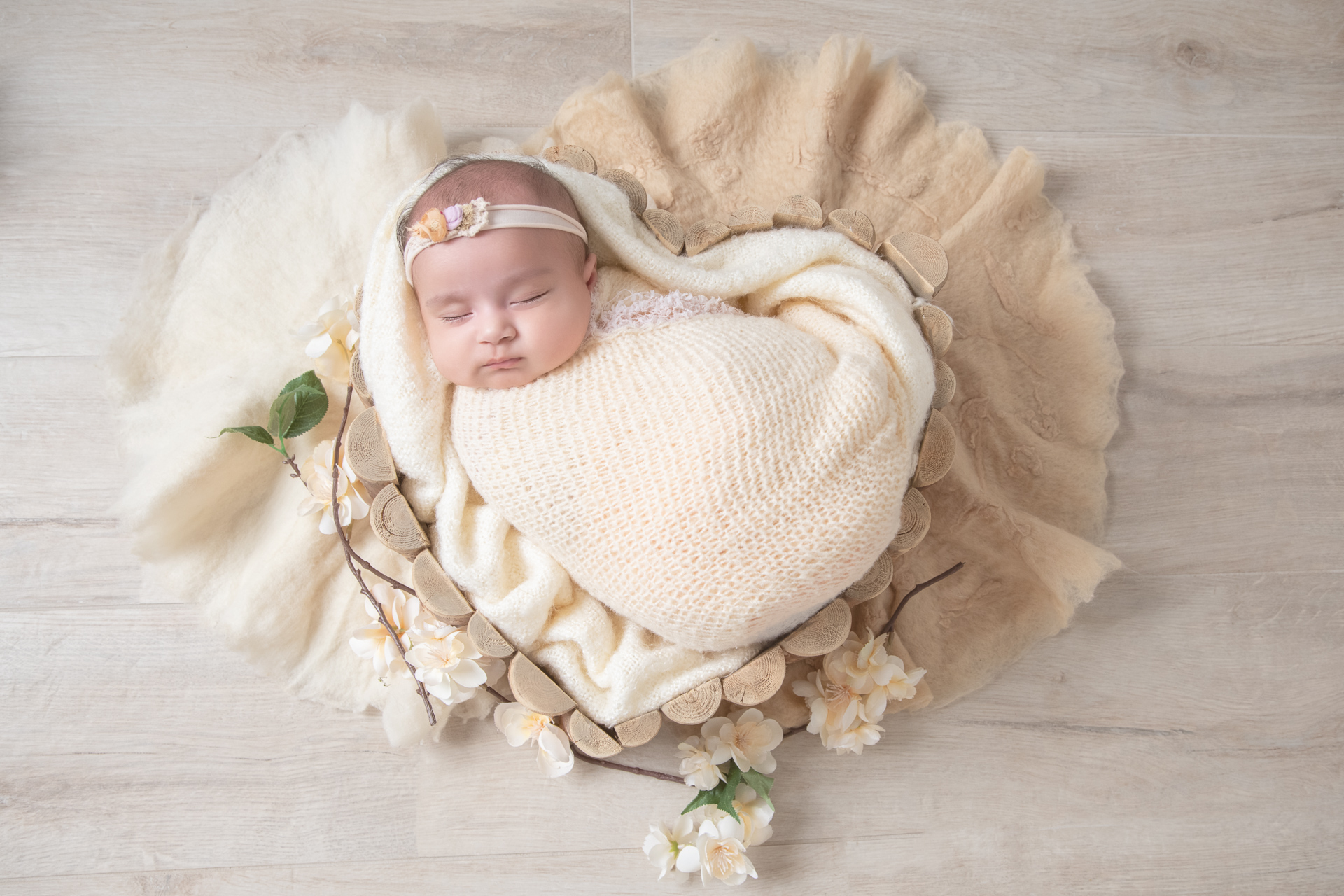Newborn wearing light beige wrap and headband rests on wood shaped prop. Flowers decorate the scene.