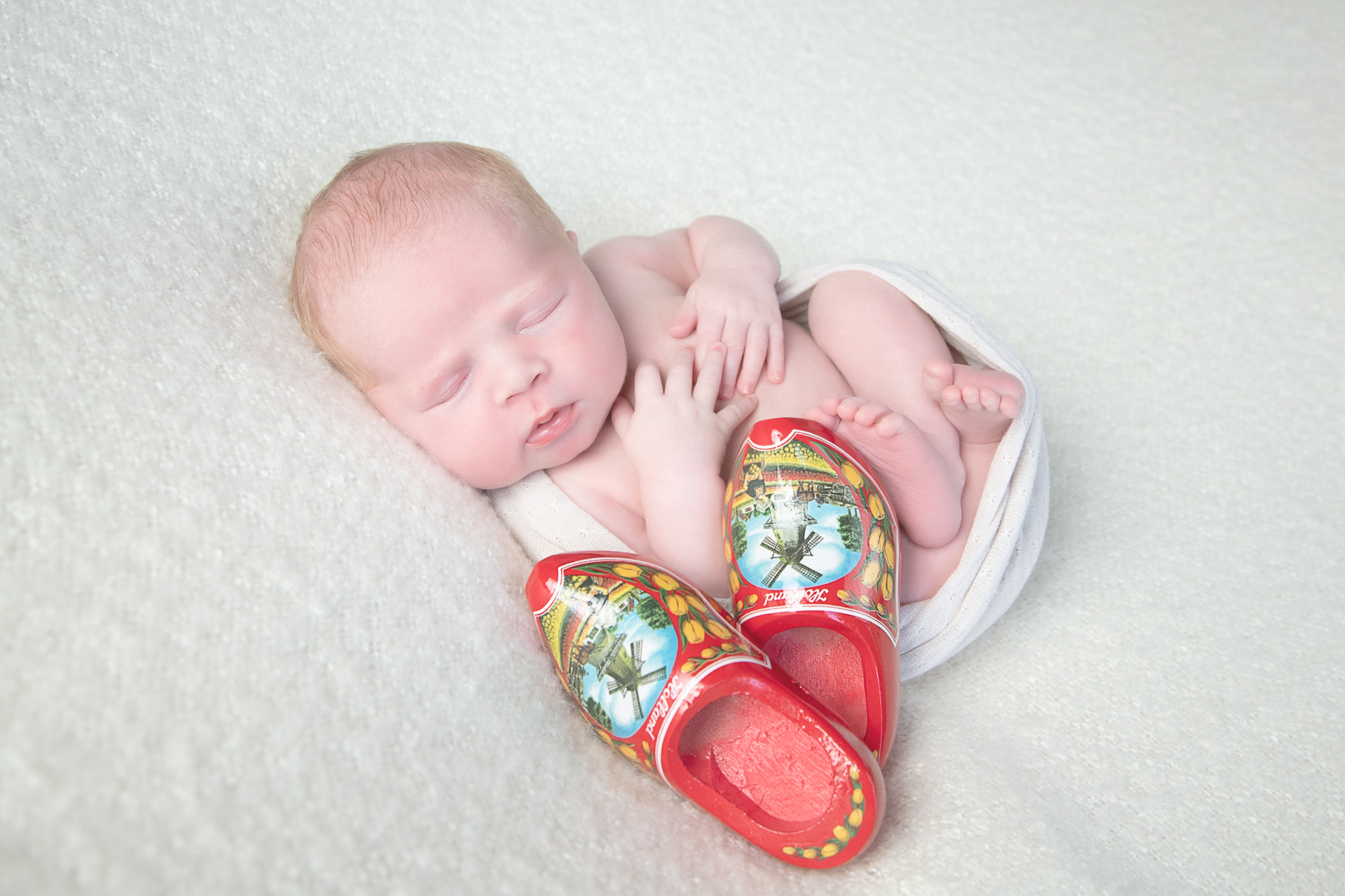 Newborn baby rests while wearing light color wrap. A pair of red shoes decorates the scene. Light beige backdrop.