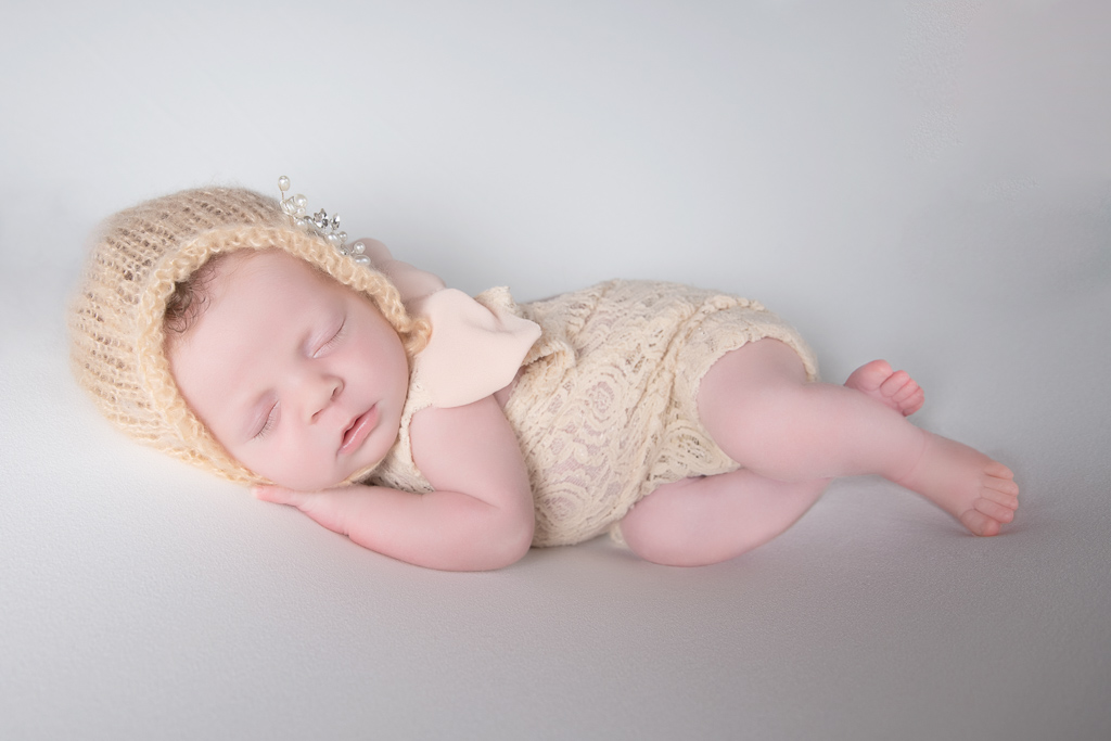 Newborn wearing yellow hat and yellow outfit rests on white backdrop.