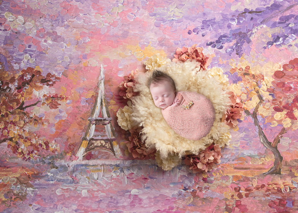 Newborn rest on a red ,pink, purple and orange tones background painting of Paris while wearing a pink wrap.