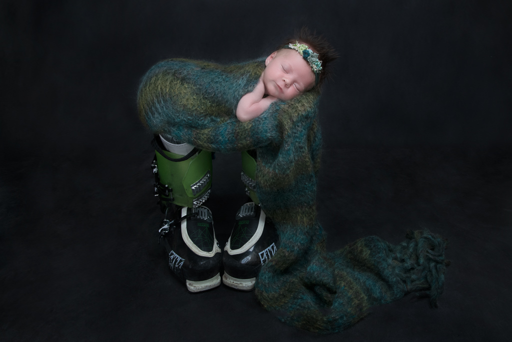 Newborn wearing green headband rests on top of green and black ski boots. Green tones blanket covers her. Black backdrop.