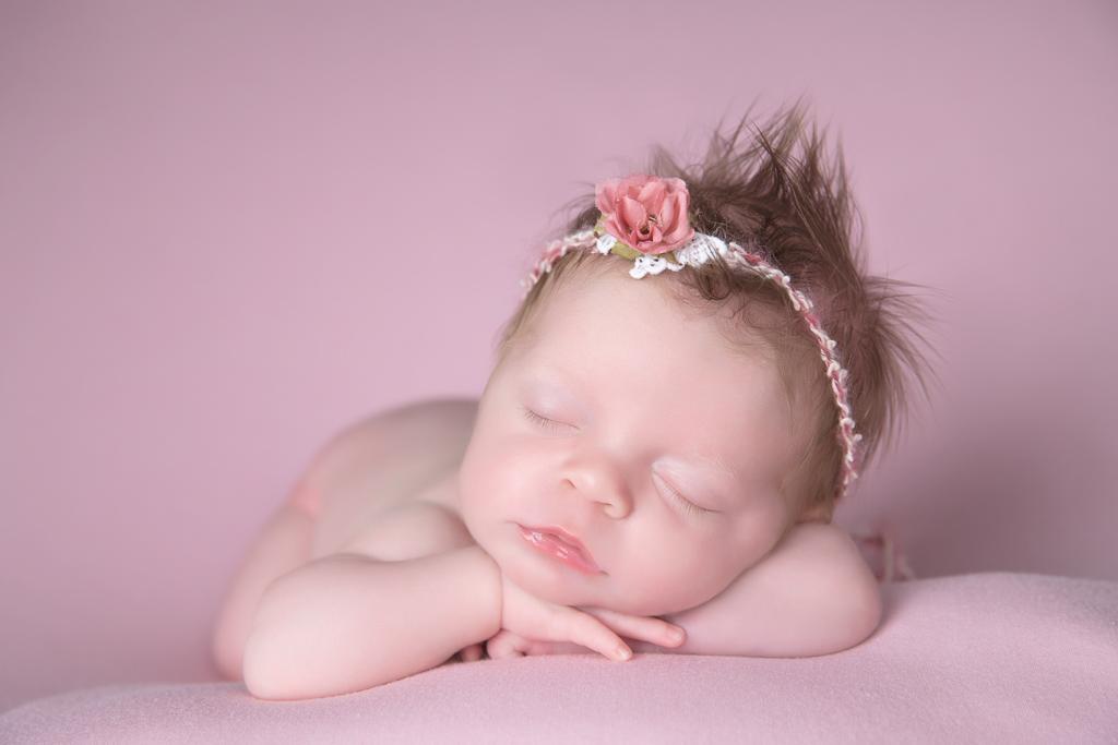 Newborn rests while wearing pink headband. Pink backdrop.