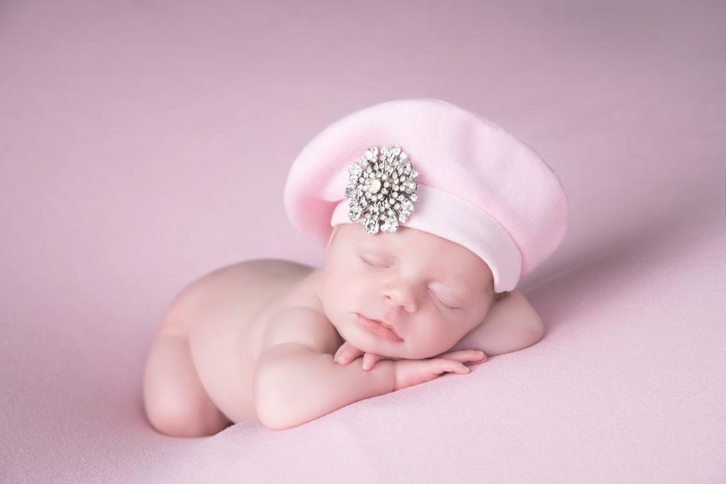 Newborn rests, wears pink hat. Pink backdrop.