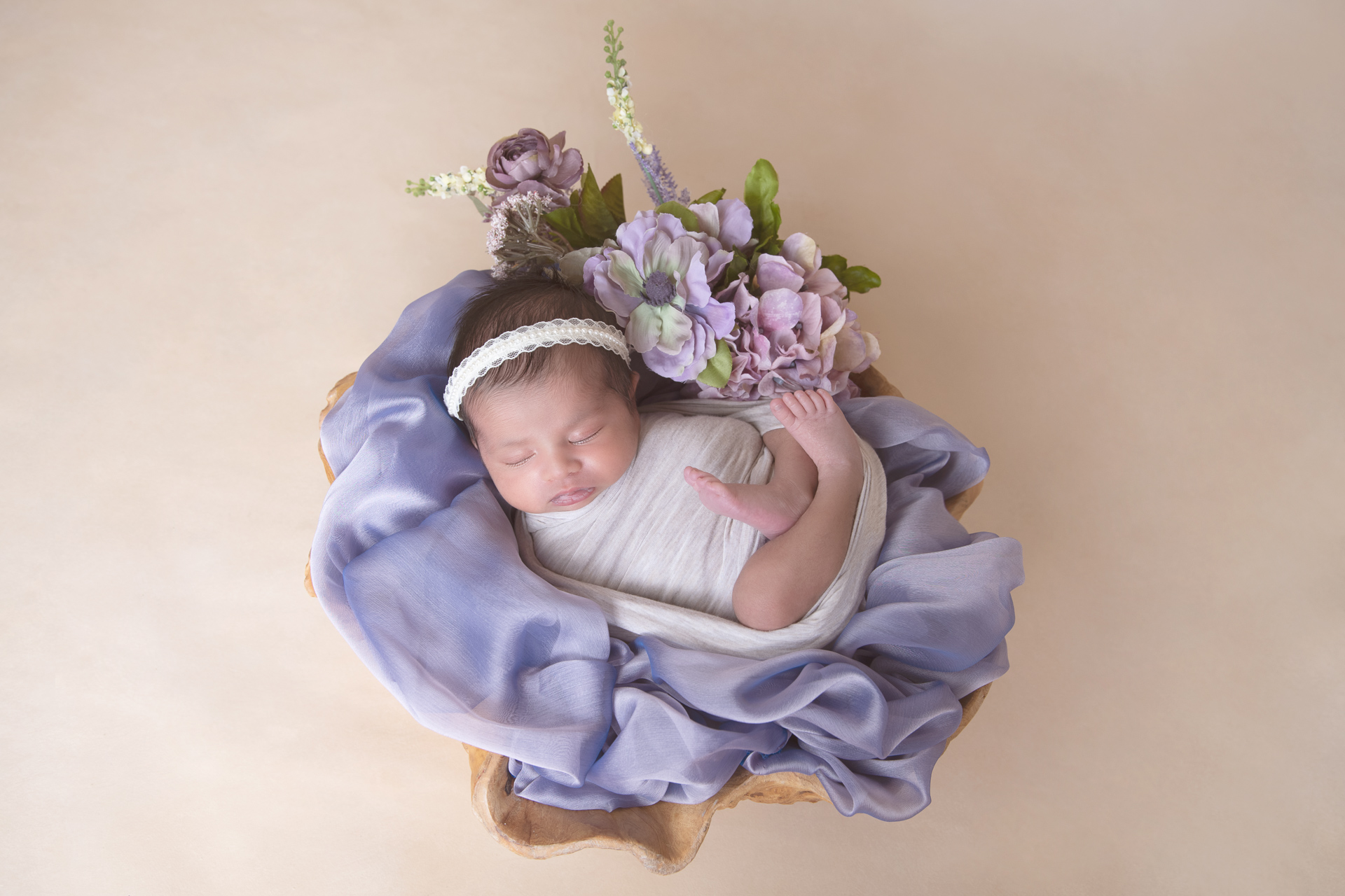 Newborn rests on irregular shape wood prop decorated by a purple fabric. She wears light gray wrap and white headband. Flowers decorate de scene.