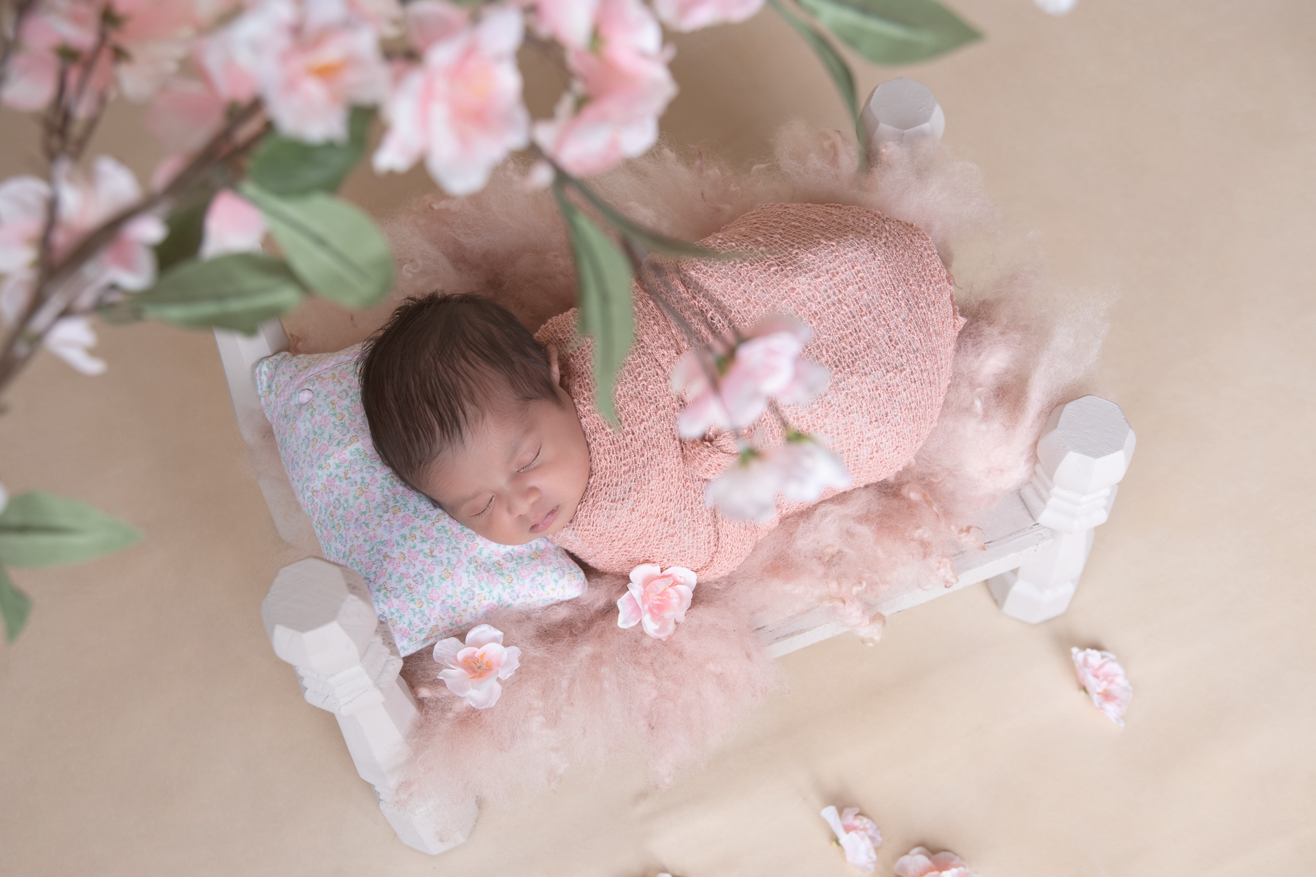 Newborn rests on bed prop while wearing pink wrap. Flowers decorate the scene. Beige backdrop.
