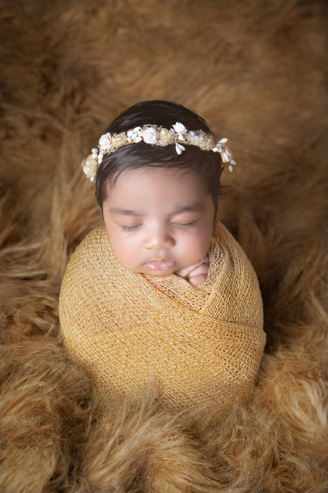 Newborn wearing brown wrap and headband rests on brown fluffy carpet.