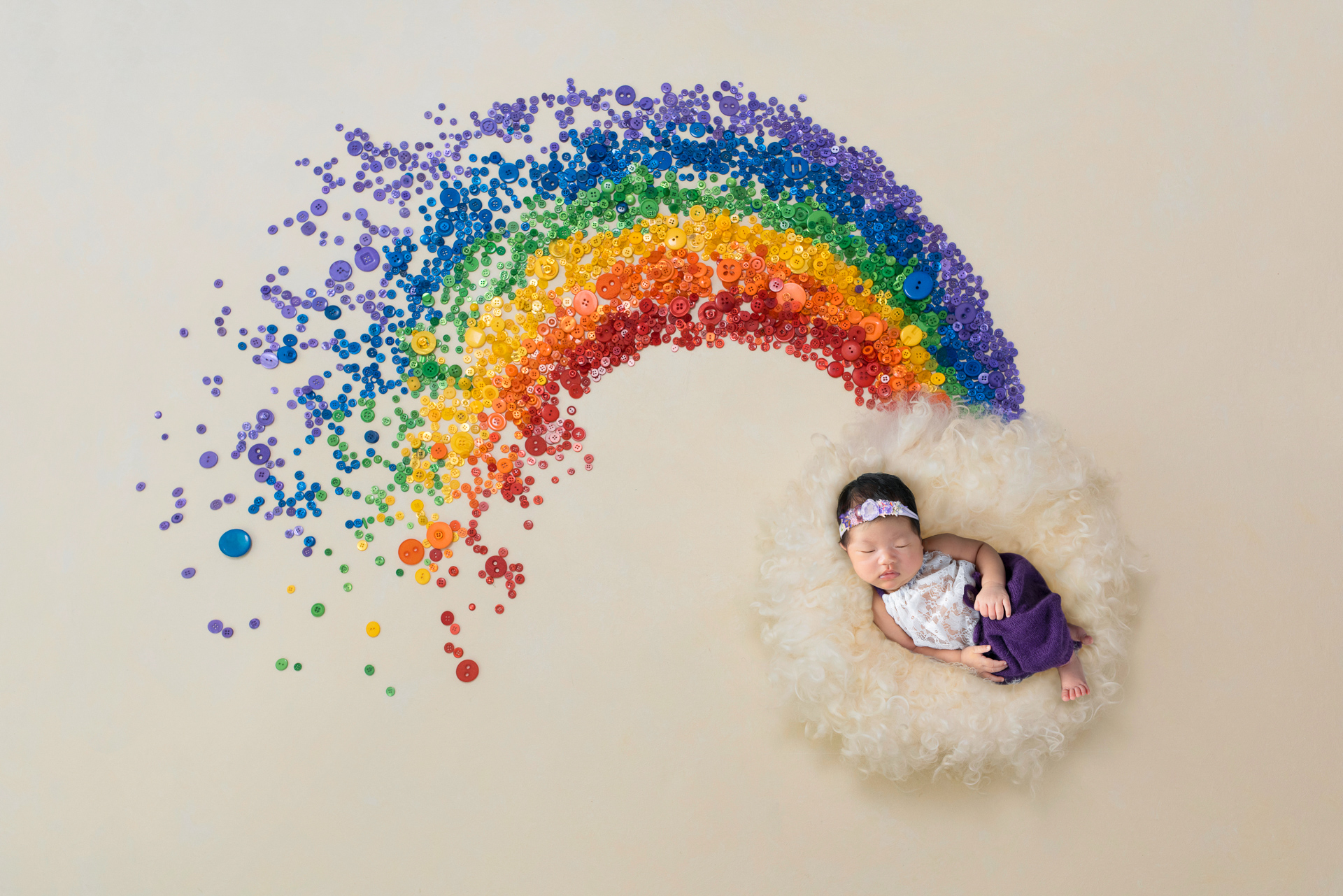 Baby wearing purple headband an white and purple outfit rest on light colored carpet from which a rainbow starts to show on light brown backdrop.