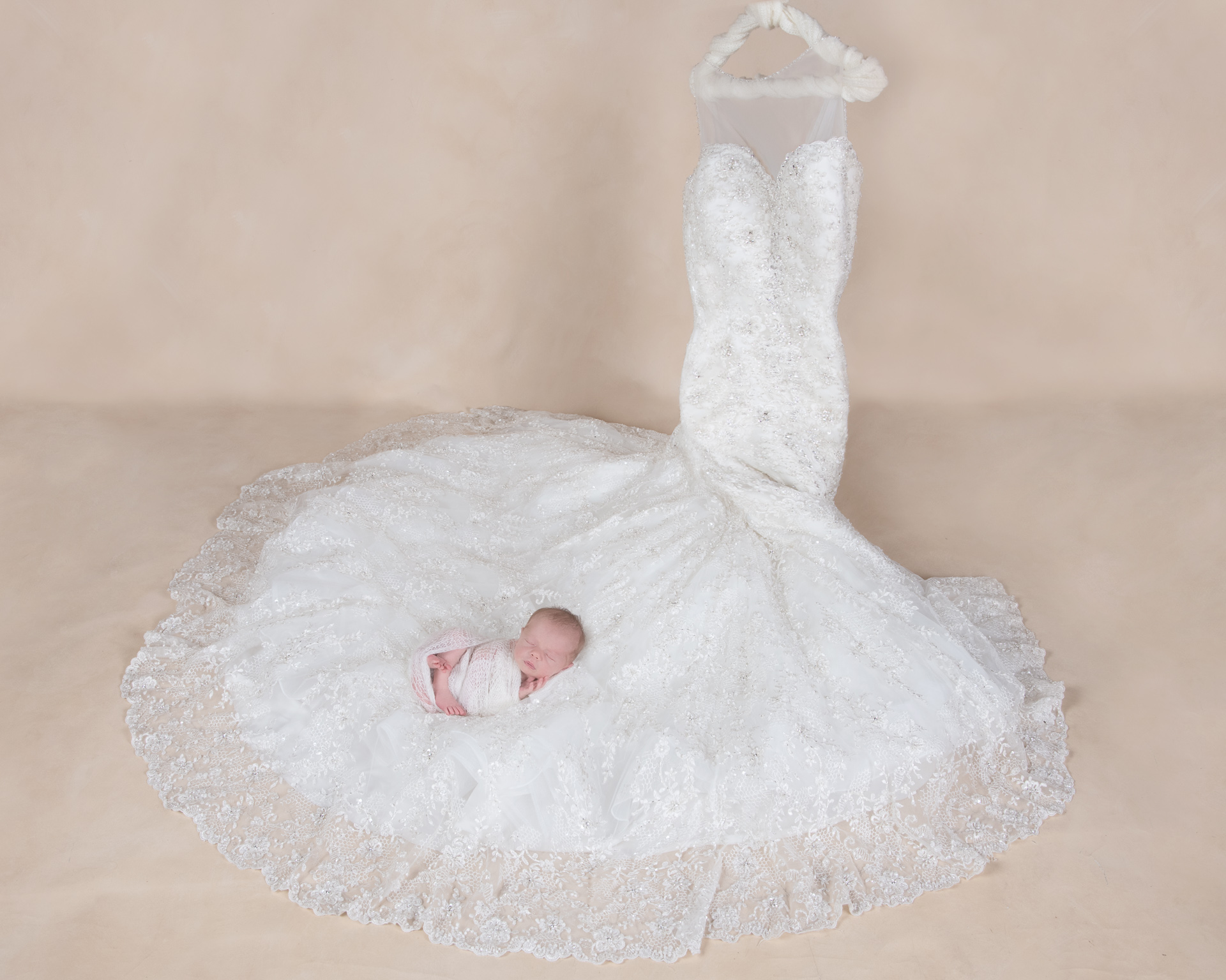 Newborn on white wrap rests on the very end of its mother's wedding dress which is placed on a hanger. Light brown backdrop.