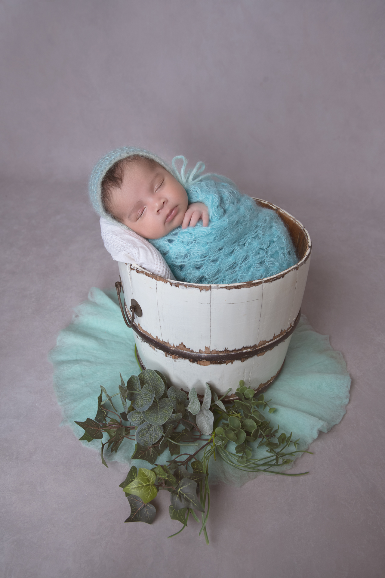 Newborn wearing turquoise hat and wrap rest on round prop basket. Gray backdrop, green leaves and green carpet decorating the scene.