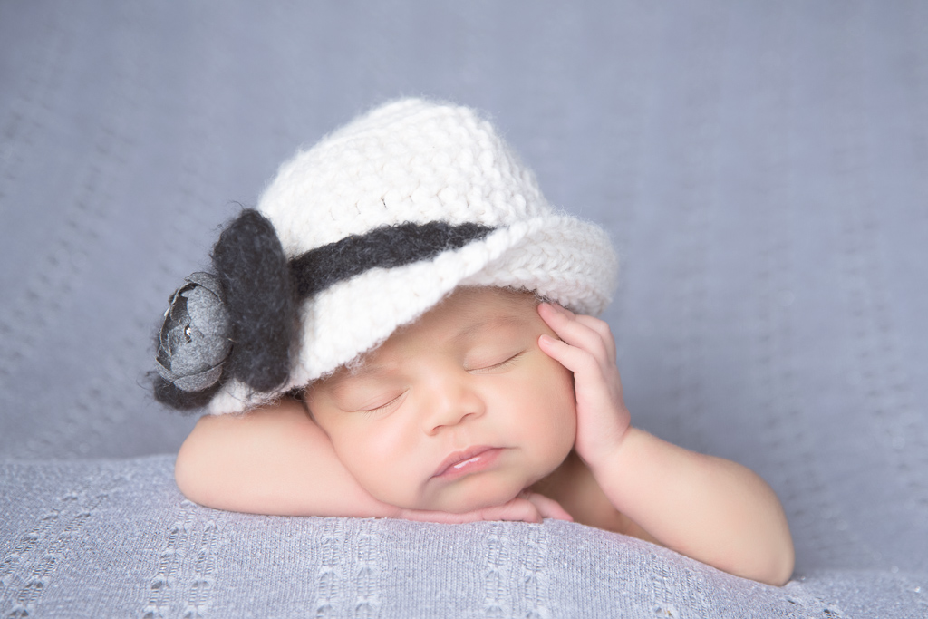 Newborn rests while wearing white and dark blue hat.